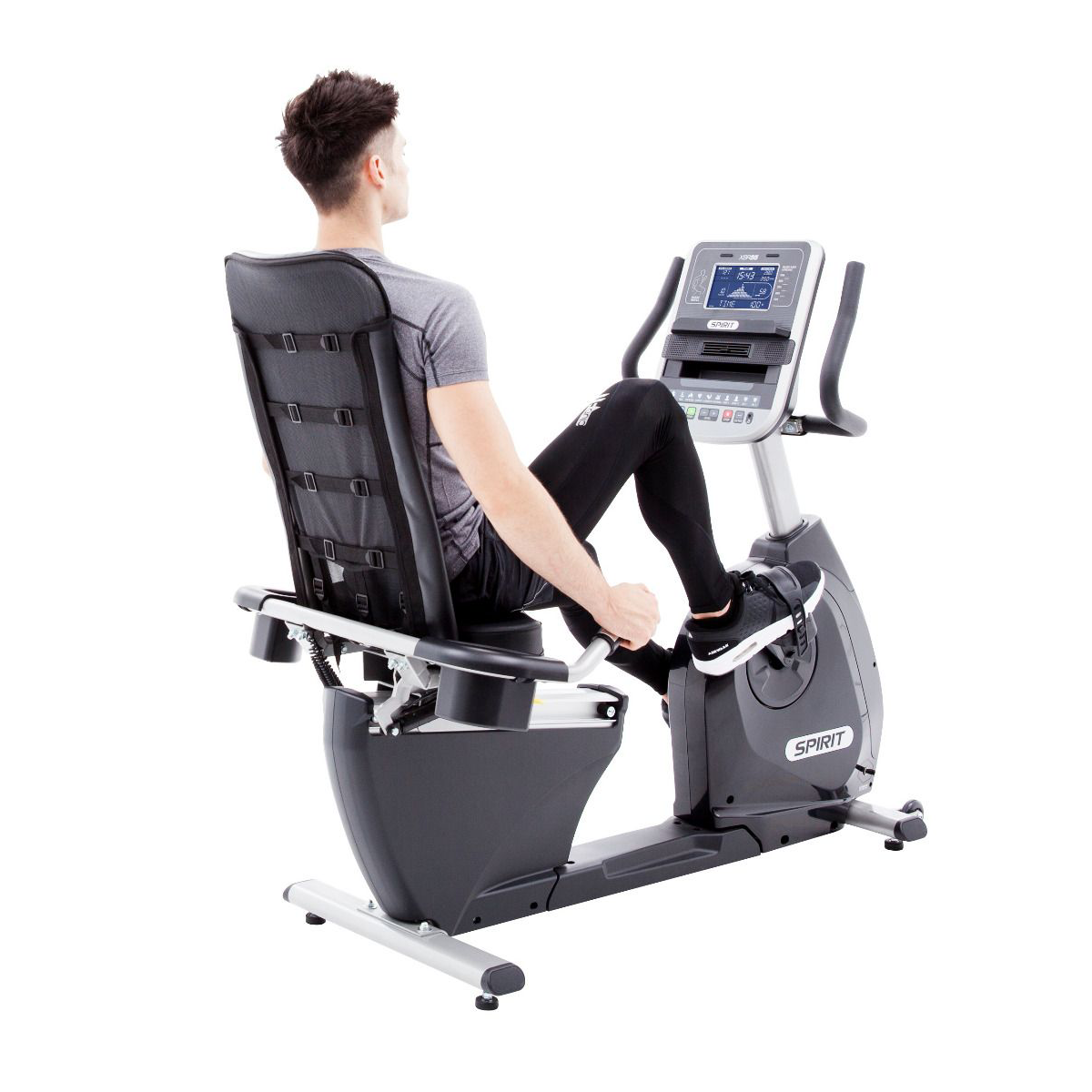 View from back/right of Spirit Fitness XE795 Recumbent Bike Trainer featuring a female model exercising while wearing a black sports bra and black shorts.