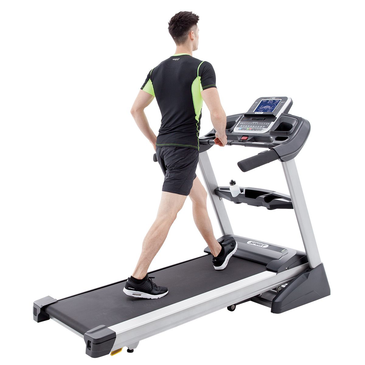 Right side/back/overhead view of the Spirit Fitness XT485 treadmill featuring a male model wearing black/green workout top and black shorts