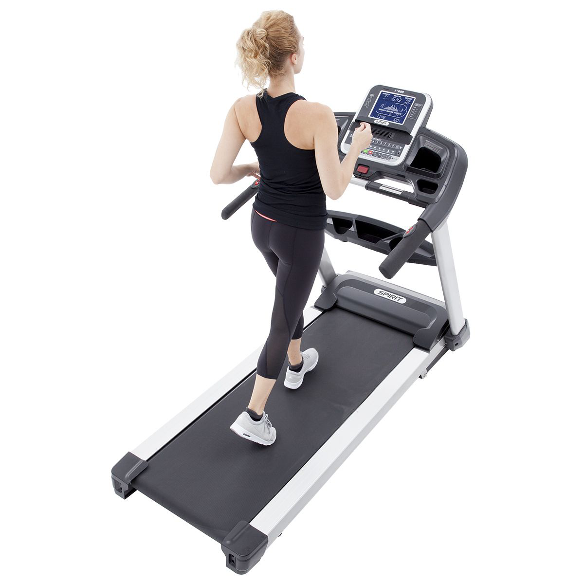 Right side/back/overhead view of the Spirit Fitness XT685 treadmill featuring a female model wearing black workout top and leggings