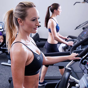 Blonde woman with ponytail wearing black tank top works out on an elliptical in the foreground while brown haired woman with ponytail wearing blue tank top works out on an elliptical in the background.