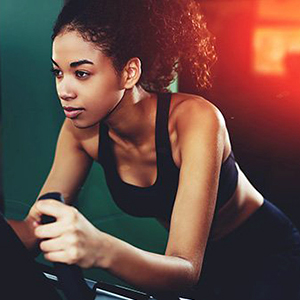 Woman with dark dair in a ponytail and wearing a black tank top works out on a HIIT machine.