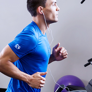 Man wearing blue t-shirt and earphones running on a treadmill.
